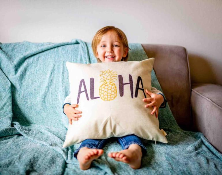"""Find out where to stay in Hawaii with toddlers. Image of a boy holding a pillow with the word """"aloha"""" on it."""