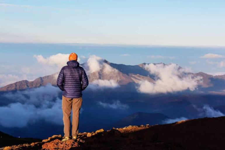 One of the best sunrises on Maui is at Haleakala National Park. Image of a man wearing a hat and coat standing at Haleakala Crater for sunrise.