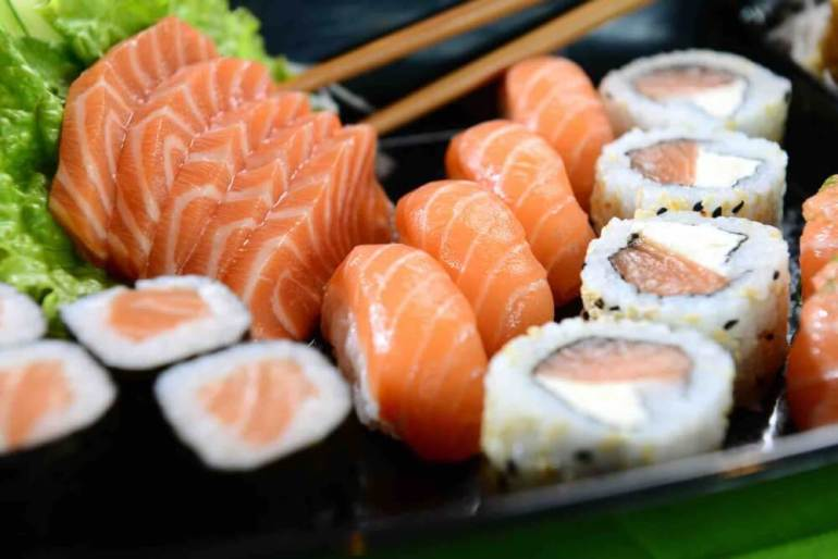 Find out where to get the best sushi in Maui Hawaii by top Hawaii blog Hawaii Travel with Kids. Image of a plate of salmon sashimi, nigiri, and sushi rolls.