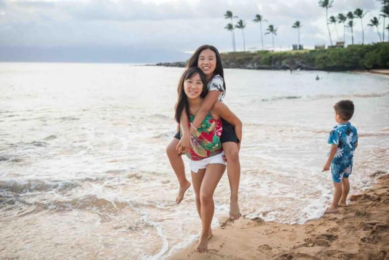 There are tons of tips for geteting awesome Maui family photos with kids. Image of two girls doing a piggy back ride with a little boy in the background