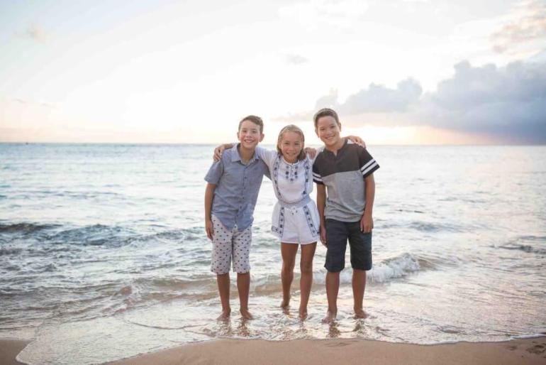 Make sure to take lots of Maui family photos with kids. Image of 3 kids posing in the water on a beach in Maui.
