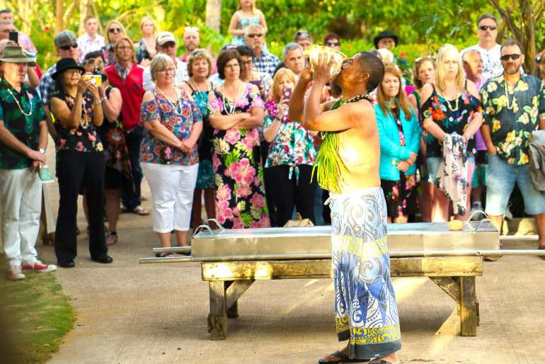 Image of a man blowing a conch shell at a Kauai luau imu ceremony.