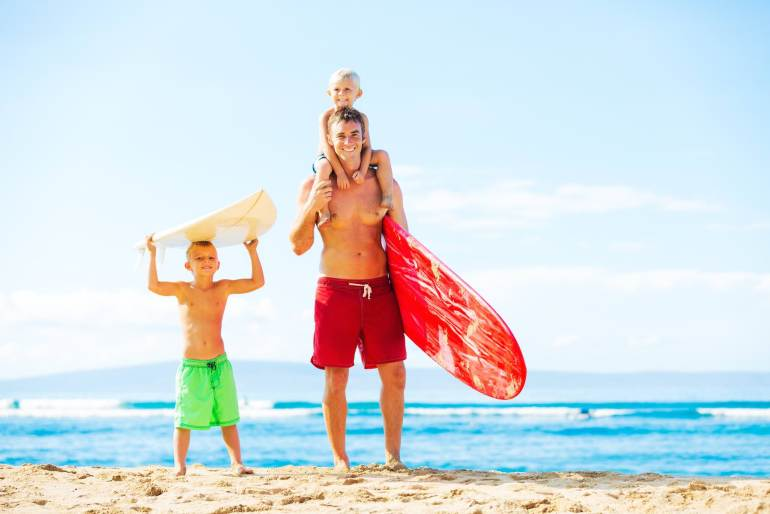 Find out where to book Maui surfing lessons for kids recommended by top Hawaii blog Hawaii Travel with Kids. Image of a father and young sons going surfing at the beach.