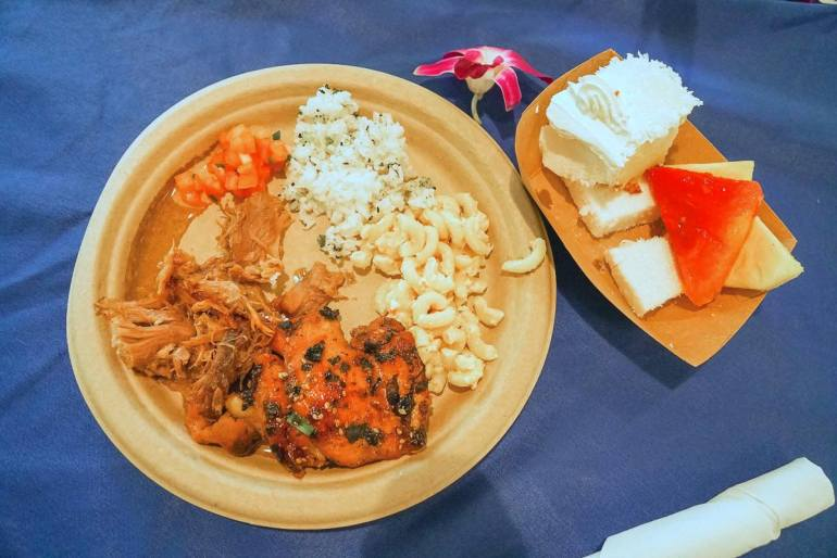 Toa Luau had some of the best luau food we're had in a long time. Image of a paper plate with teriyaki chicken, kalua pig, lomi loi salad, rice, macaroni salad, and dessert.