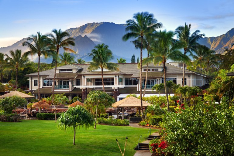 The Westin Princeville Ocean Resort Villas is one of the best resorts in Kauai for families because of its stunning location. Image of a resort in front of the mountains on Kauai.