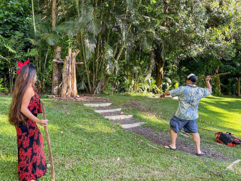 Learn how to throw a Hawaiian spear at the Experience Nutridge Luau on Oahu. Image of a man wearing an Aloha shirt throwing a spear at a target.