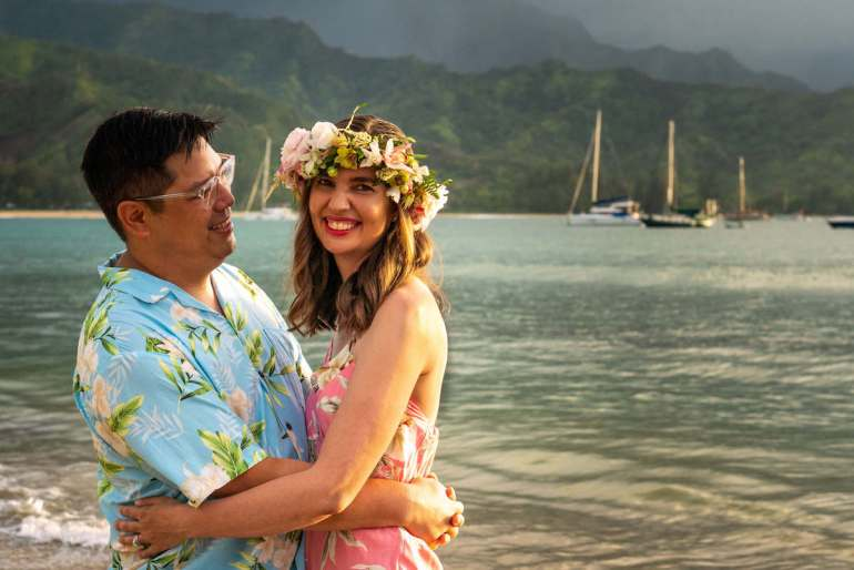 """Make sure to get a few """"couple shots"""" during your Hawaii photographer shoot. Image of a man and woman embracing on a Kauai beach."""