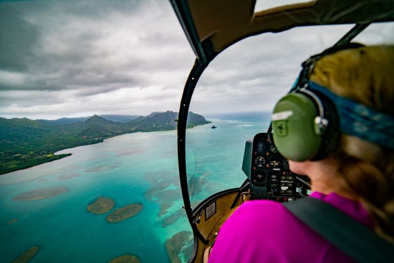 Find out the best private Oahu helicopter tour worth booking. Image of a woman riding in a doors off helicopter ride on Oahu.
