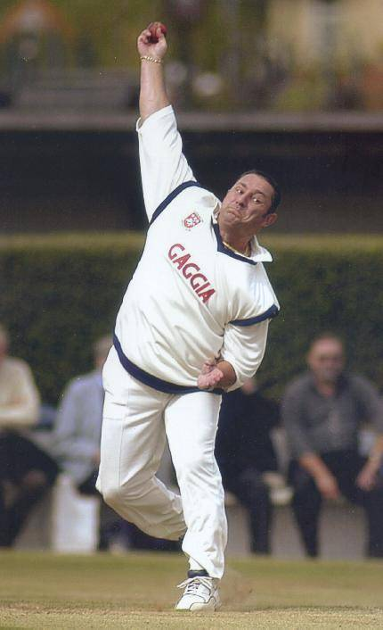 Shane Warne takes a sharp catch midway through his bowling action.
