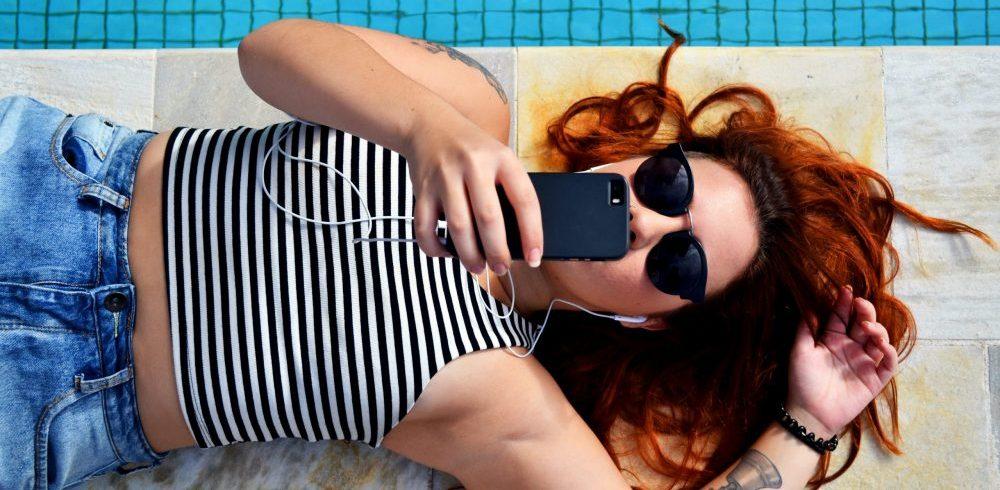 girl by pool looking at social media