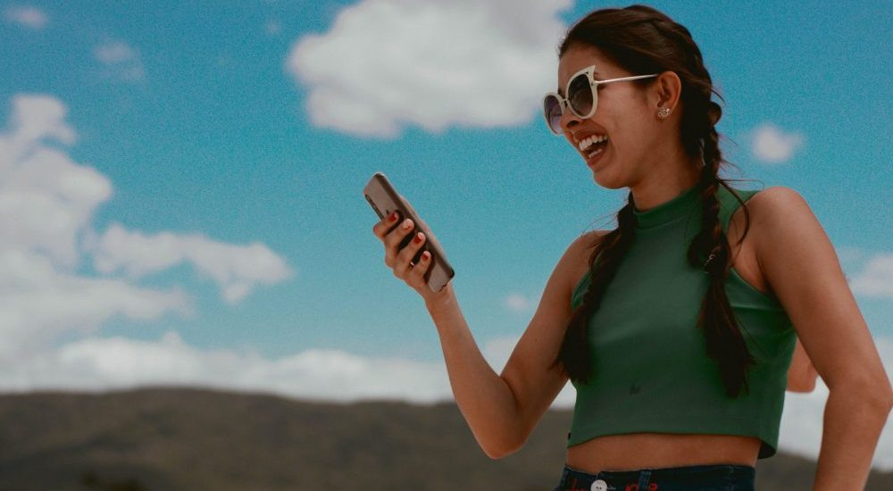 girl outside smiling at phone