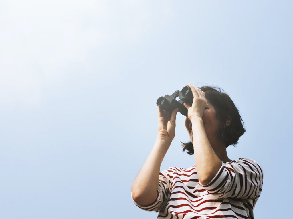 woman searching with binoculars outside