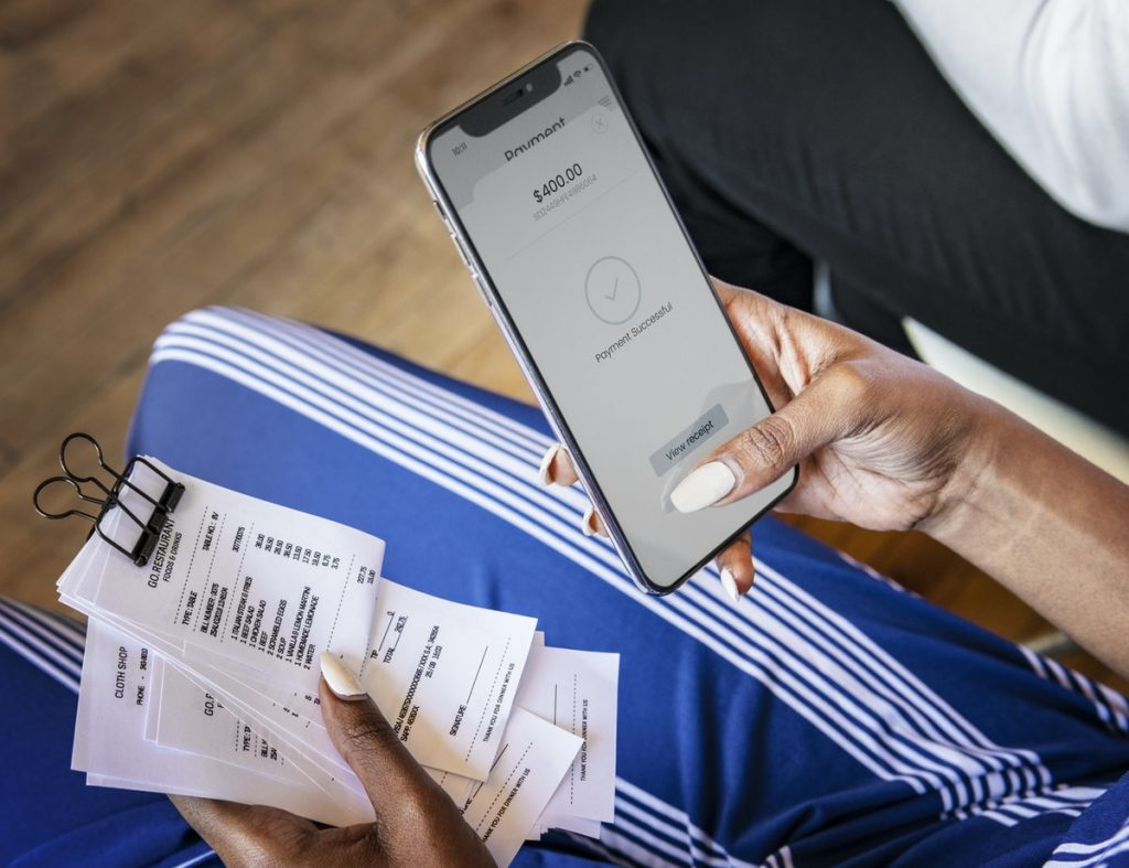 woman calculating receipts with smartphone