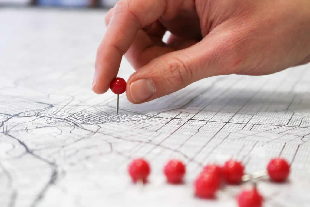 hand putting pins in a map
