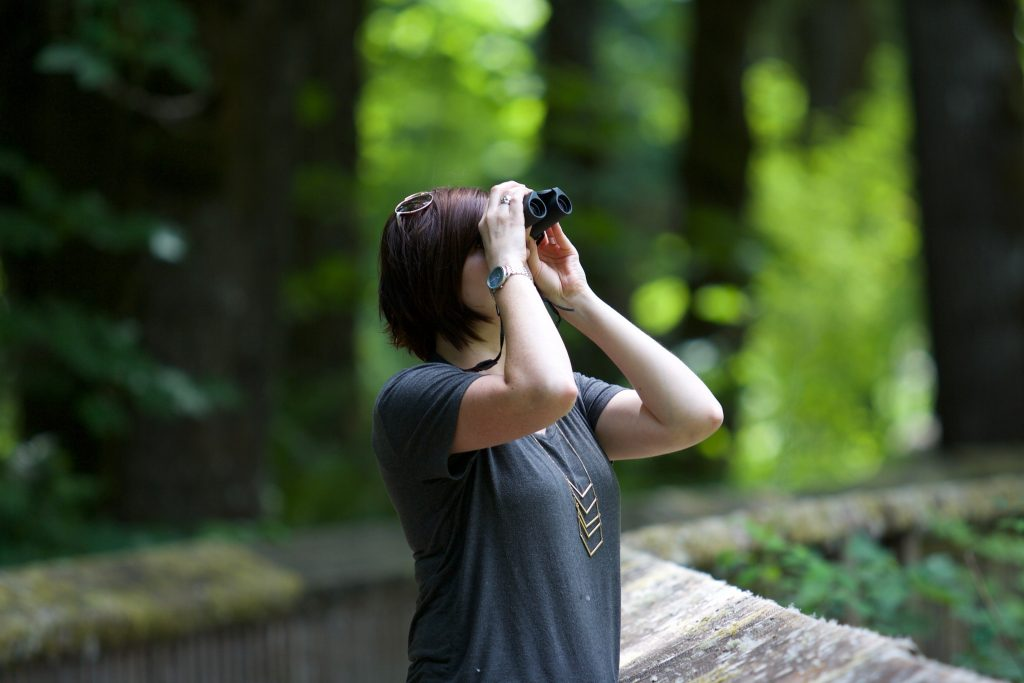 woman searching with binoculars in the woods