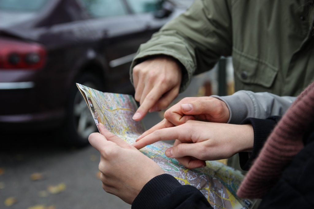 three people's hands pointing at a map
