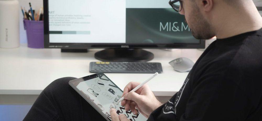 man designing a website on a tablet