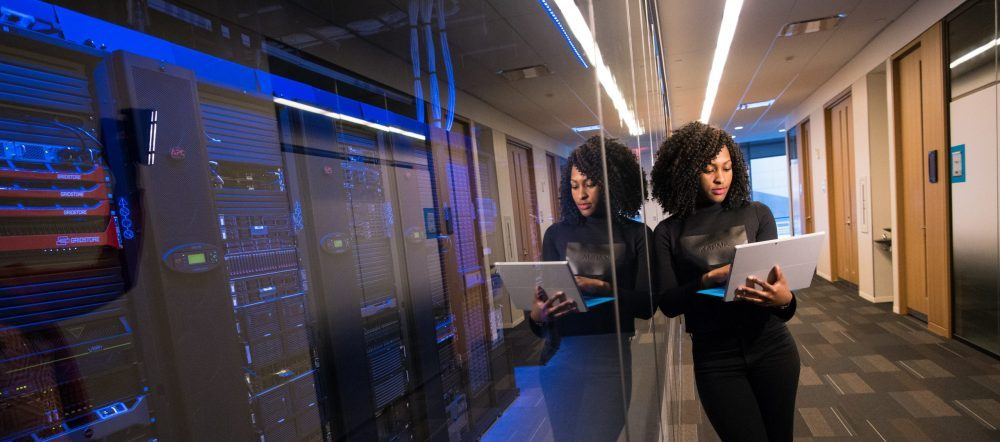 woman standing in a hallway using her laptop next to data