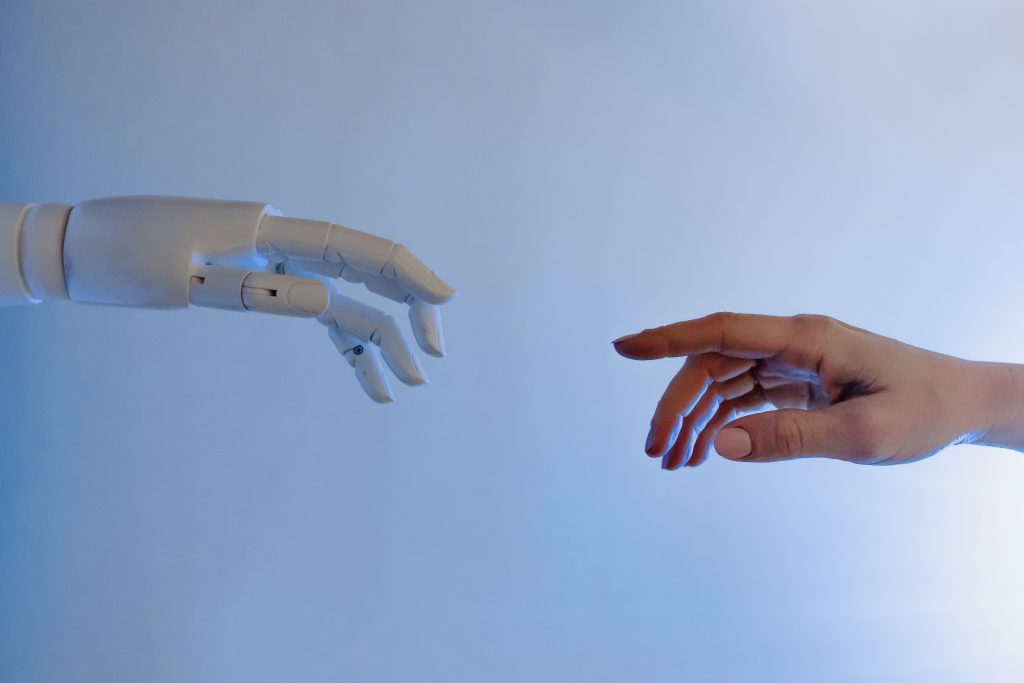robot and human hands reaching for each other