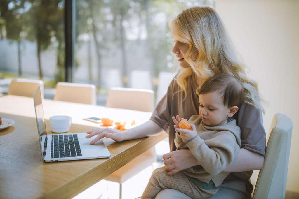 woman holding baby and working on a laptop while sitting at a table