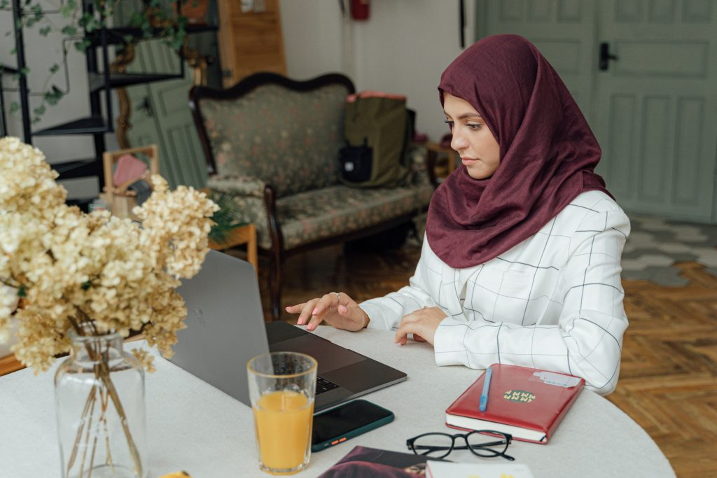 woman sitting at a table on laptop computer