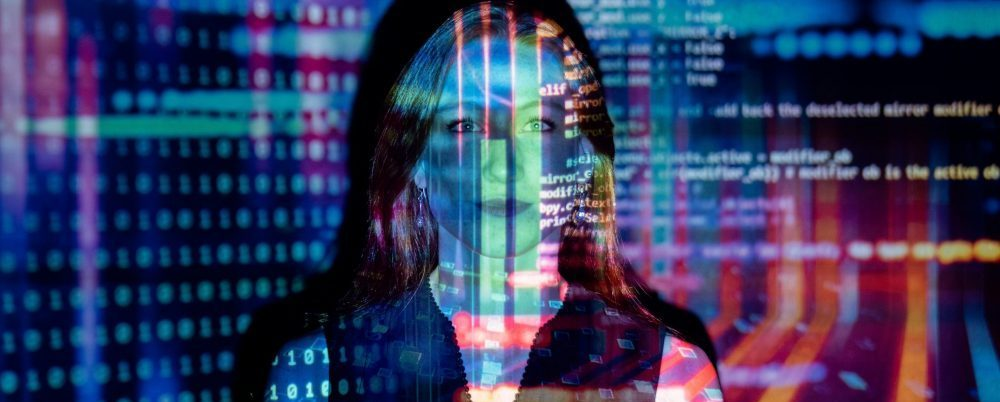 woman in front of a wall with a colorful data projection