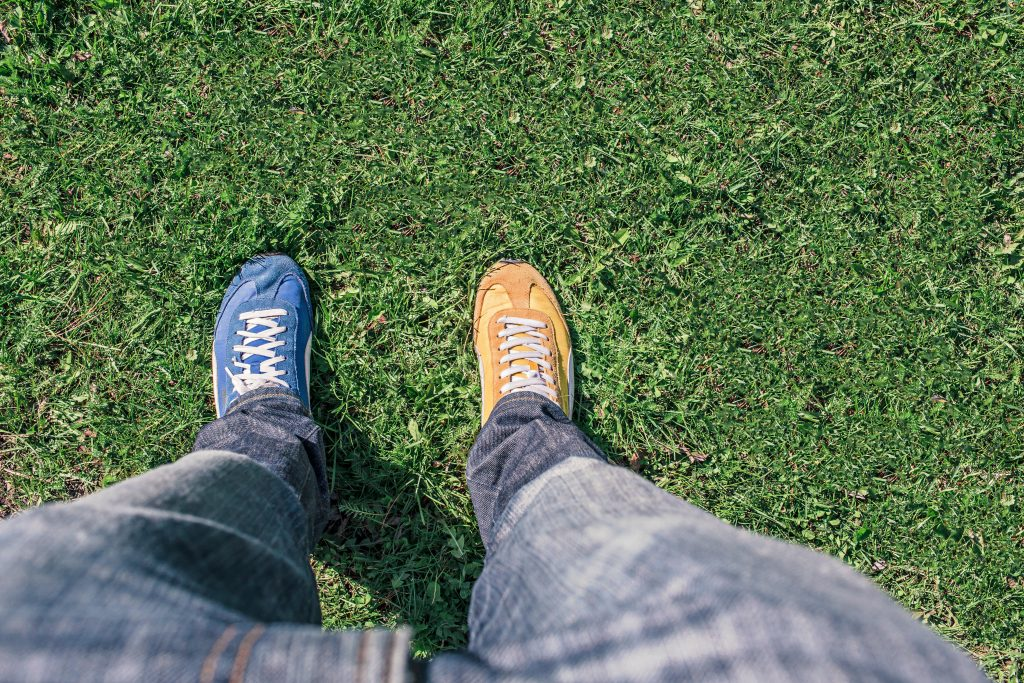 person wearing one blue shoe and one yellow shoe on grass