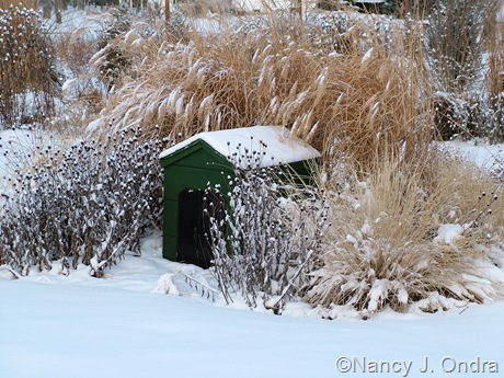 Faux dog house with rudbeckia, miscanthus, and pennisetum in snow