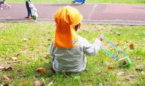 芝生に座る子供の後ろ姿