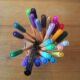 directly above fine pens with caps in an array of colors, arranged in a small glass jar which is just barely visible below the pens, and all sitting on a light wood table