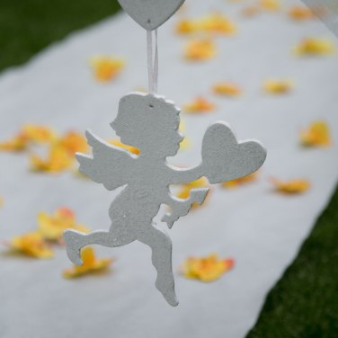 Cupid wedding decoration in front of white wedding aisle runner with yellow flower petals