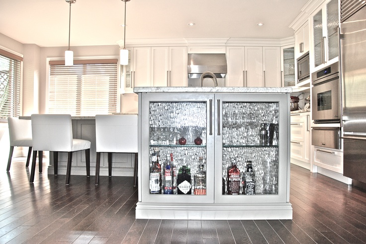 "Who says you can't have a glitzy bar in your kitchen? Here, the end of an island is transformed into that cabinet (and we kind love that background that screams ""party"" too). See more at DC Renos »"
