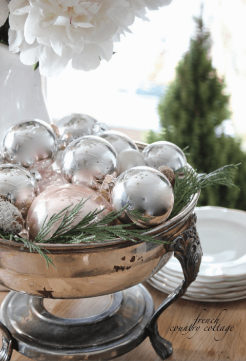 Tuck shiny silver ornaments onto a bed of greens to make their brightness pop even more. See more at French Country Cottage »