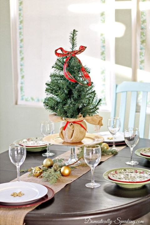 Go all out for a holiday table centerpiece, and place a miniature evergreen — topped with a ribbon — in the middle of your spread. See more at Domestically Speaking »