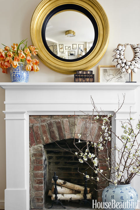 A bull's ­eye mirror by Carvers' Guild surveys the living room from above a custom mantel painted in Benjamin Moore's White Dove.