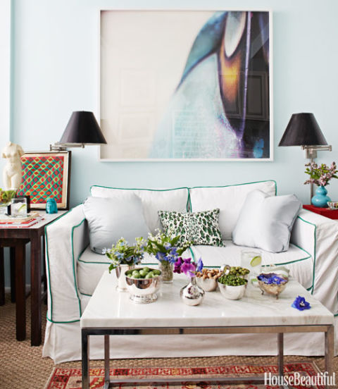Petite living room with pale blue walls, bold art, and swing-arm sconces above the sofa. As seen in House Beautiful, designed by Nick Olsen,