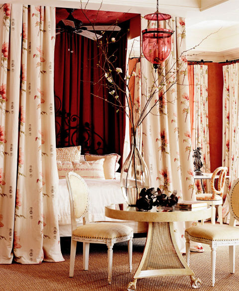 "<p>""I wanted it to be, above all, romantic,"" designer Barry Dixon says about this master bedroom in a <a href=""http://www.housebeautiful.com/decorating/makeover-impact-0208"" target=""_blank"">Maryland house</a>. ""I thought of being inside a conch shell, and used all those colors. The sheers on the windows cast a rosy glow on everything in the room, and there's that wonderful red lantern. Everyone looks rosy and tan in there, even if they're not."" Floral bed hanging and window panels are Fragrance by <a href=""http://www.sanderson-uk.com/"" target=""_blank"">Sanderson</a>. The Nettie Darr table at the foot of the bed is by Barry Dixon for Mike Reid Weeks. Sophie side chairs, upholstered in raffia are from <a href=""http://www.olystudio.com/"" target=""_blank"">Oly</a>. Asian bedside tables from <a href=""http://bungalow5.com/"" target=""_blank"">Bungalow 5</a>.</p>"