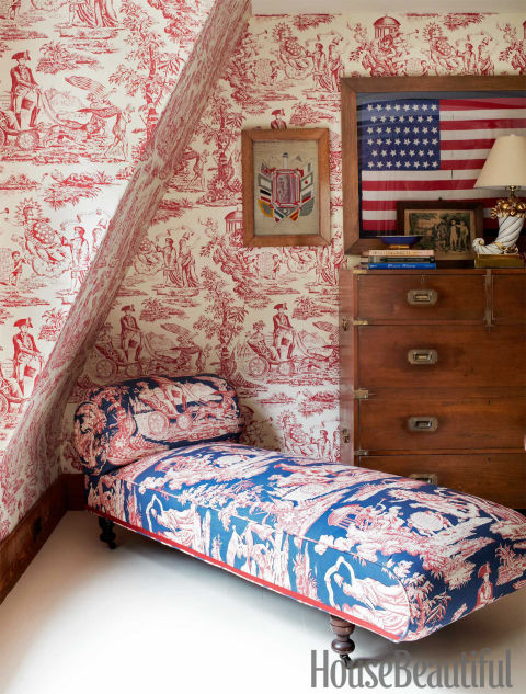 In John Knott and John Fondas's Maine master bedroom, the patriotic theme sprang from Fondas's collection of Washington memorabilia and American flags. Independence Toile covers the daybed next to a 19th-century English campaign chest. Walls are covered in Quadrille's Independence Engraving.