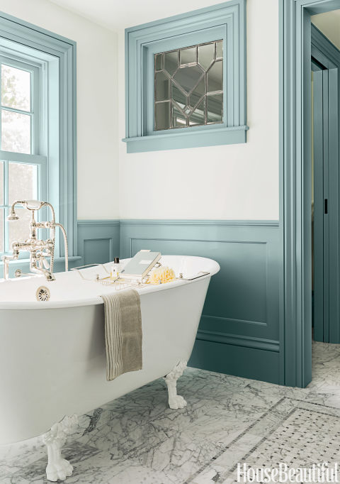 """Back in the 18th-century when this Massachusetts farmhouse was built, there was no such thing as a master bath. So architect Michael T. Gray and interior designer Hattie Holland, both of Carpenter & MacNeille, carved one out of a hallway and added wainscoting and window casings to create a sense of the past. Painted a deep blue-gray, they stand out against the pale blue walls. The color """"has a historic feeling with that gray cast and plays off the Carrara marble so well,"""" Holland says. In the center of the floor, a virtual rug made of marble in a basket-weave pattern adds another layer of detail to the room. The cast-iron tub looks old but is actually new. """"It's a slipper tub, higher on each end, and that little swoop gives it a sense of elegance,"""" Holland says. """"And the legs let you see the marble underneath, which makes a small space feel more open."""" An antique leaded-glass window, found at a salvage yard, is set into the wall adjoining the water closet. It lets light into that room, making it feel less enclosed while still maintaining privacy. It's another old-world touch that creates instant character. """"The goal was to keep the farmhouse charm but make it more comfortable,"""" Holland says. """"You can lean back against that great rollover on the tub's rim and soak for hours."""" The Missy tub is paired with a floor-mounted tub filler in polished nickel, both by Sunrise Specialty. Carrara marble tile and basket-weave insert from Cumar. The walls are painted in Borrowed Light with trim in Parma Gray, both by Farrow & Ball."""