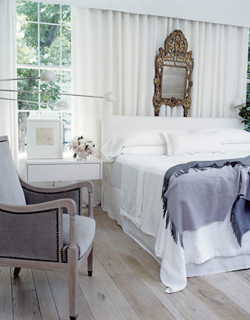 "In the master bedroom, ""the light fixtures and mirror have center stage, so the wall-mounted bedside tables had to float quietly,"" says Brown. Bedside lights ""are big sconces, basically,"" from David Weeks in New York."