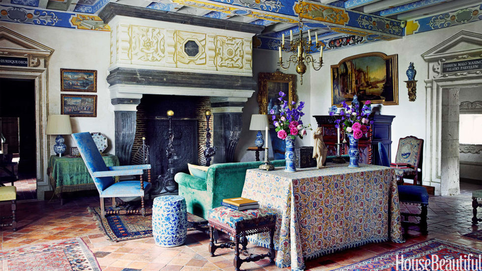 In renowned conductor William Christie's 16th-century house in France, color and pattern are not confined to the fabrics — they reappear on the walls and even the ceiling, painted in a glorious trompe l'oeil by François Roux. In this room, Roux mixed the motifs of Christie's two great passions, music and gardens. The 19th-century French chandelier was inspired by a 17th-century Dutch original. An antique fabric covers the table.