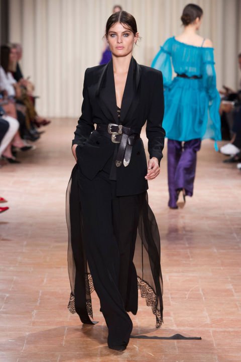 For spring, the designer mixed sophisticated separates into her gown mix, via variations of a slouchy black slouchy tuxedo, sometimes done with embellished sleeves and a lacy train. Elsewhere shot silk or lacy tailored pants felt like one thing too many under dresses in colorful tulle or black lace.
