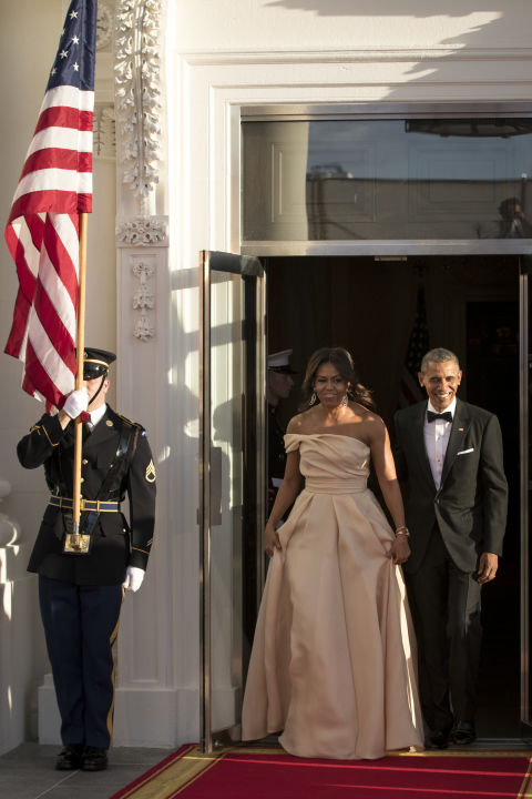 Michelle Obama again opts for a gorgeous dress by Naeem Khan, this time in a blush color with an asymmetrical neckline.
