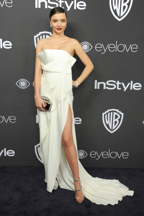 Perhaps bride-to-be Miranda Kerr is using the various red carpet appearances she has in her schedule to sample silhouettes of looks she's entertaining for the aisle? This strapless look by August Getty seems standard at first glance, but an open-back, draped bodice and thigh-high slit gives it an added dose of sex appeal.