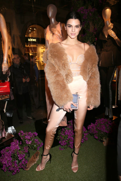 In a lace lingerie top, tan fur coat, champagne-colored pants and two-tone heeled sandals at the La Perla store opening in Milan.