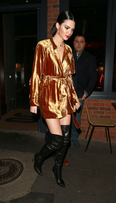 In a metallic gold velvet wrap dress, black leather over-the-knee boots, layered necklaces and gold hoop earringsafter her LOVE Magazine signing in London.