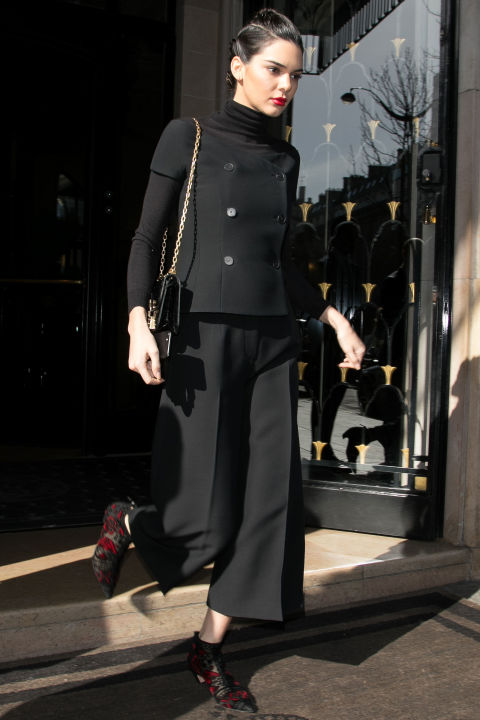 In a black turtleneck under a buttoned top with wide leg trousers and red and black printed boots while out in Paris.