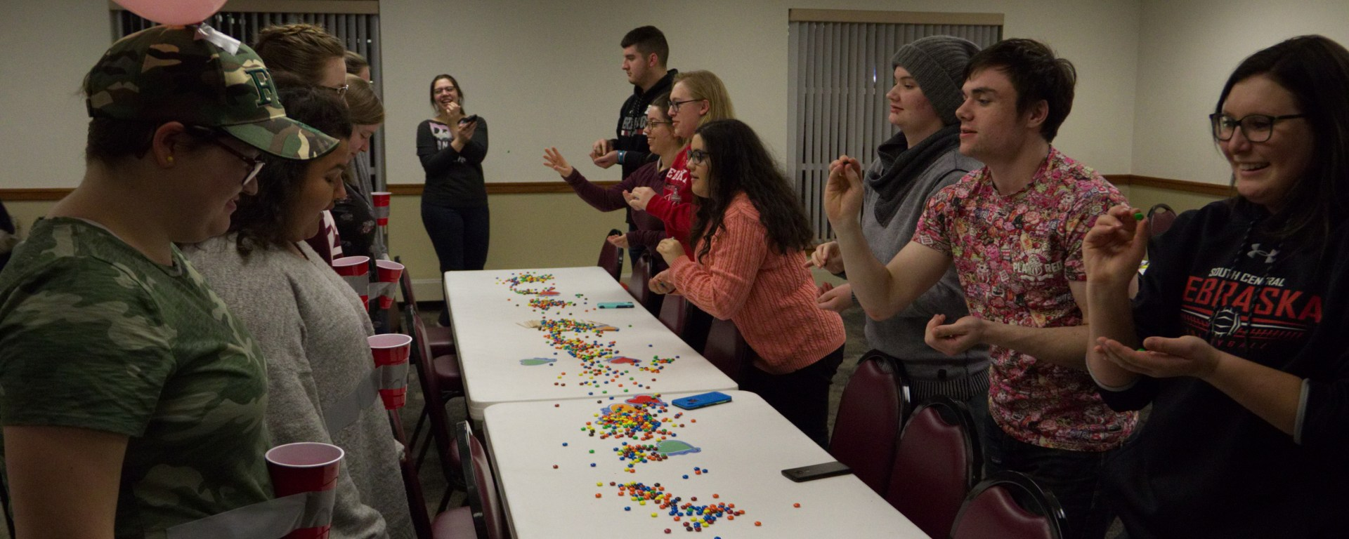 Students compete to throw the most M&Ms into a cup taped around their partner's waist
