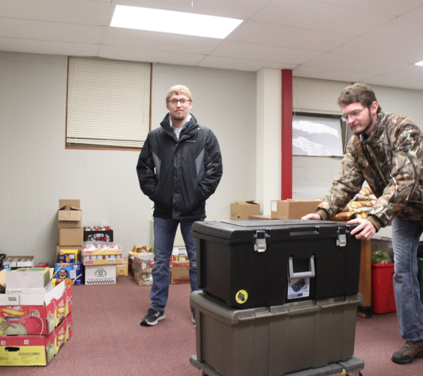 Parker Grant (left) and Joe Jahn (right) take away bins of food for Longfellow Elementary School as part of the Food4Thought program.