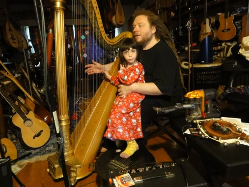 Jaron Lanier at home in the Berkeley, CA hills playing harp with his daughter, Lilibell, in October 2010.